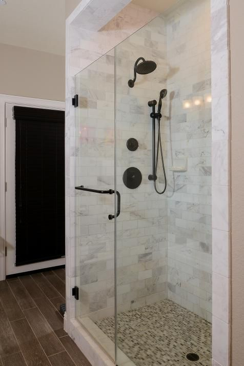 This glass-enclosed shower features beautiful Carrara marble tiles, bronze fixtures and a neutral mosaic tile floor. The bathroom's neutral walls and soft brown floors coordinate beautifully with the shower.