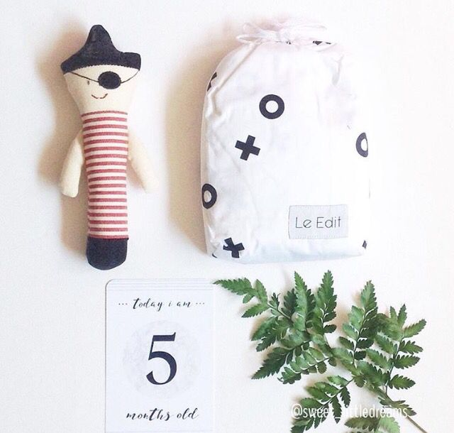 Baby boy flat lay featuring pirate rattle, xo cot sheet and milestone cards. www.sweetlittledreams.com.au
