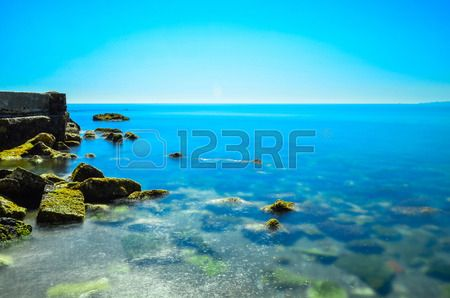 Beach of crystalline Water with rocks on the left side.