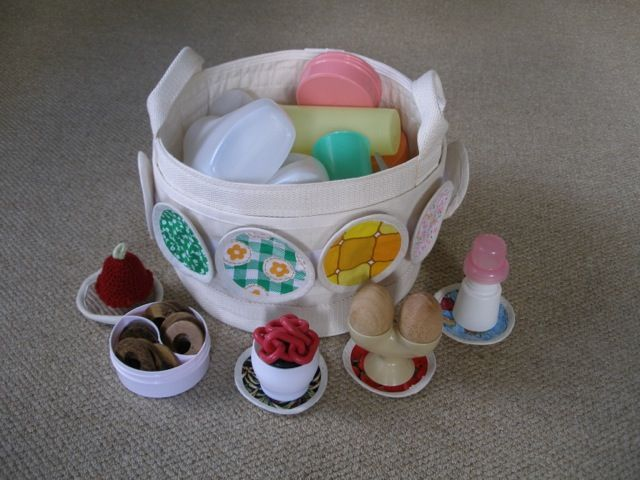 plainlycanvas 'small floor storage bag and fabric circle set' with a collection of plastic containers (recycling numbers 2 and 5 preferable), plus wooden eggs, a crochet egg cosy, plastic chain, wooden rings.