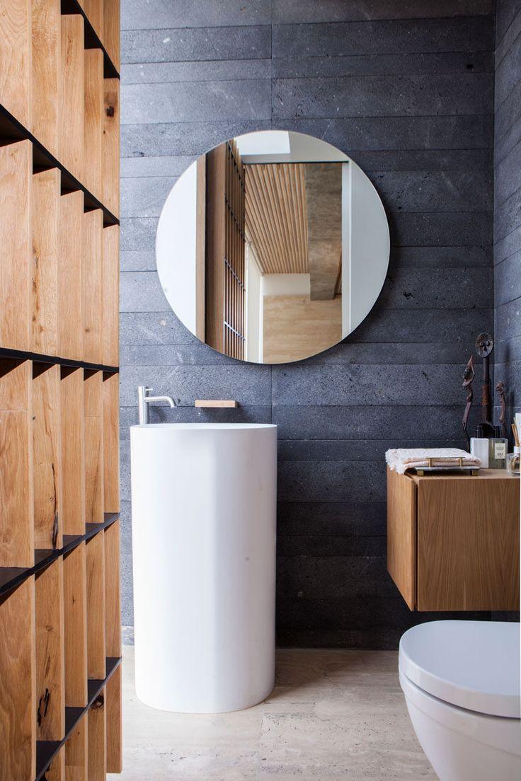 這個現代化的浴室配有深灰色的瓷磚和木頭,配有簡單的獨立白色的洗手盆和衛生間。