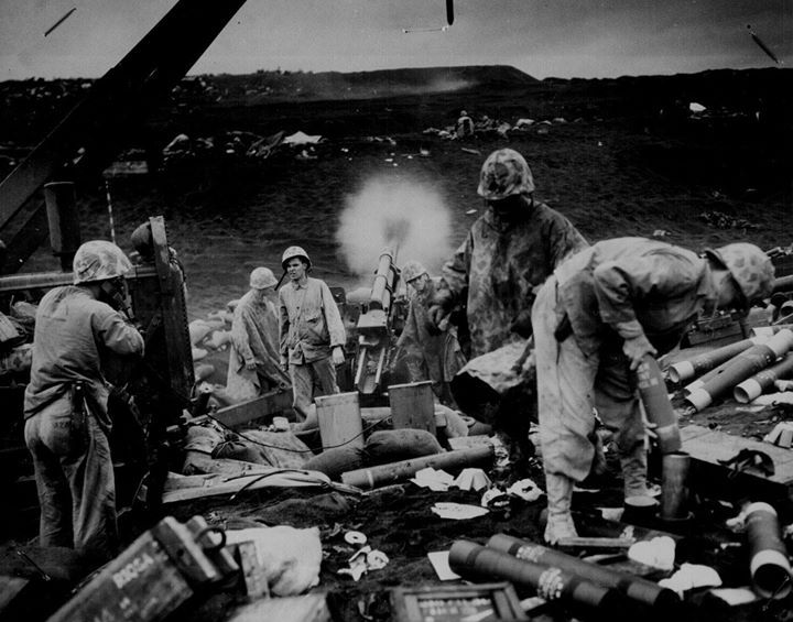 Men of US Marine Corps 4th Division shelling Japanese positions from the beach Iwo Jima Japan February 1945.