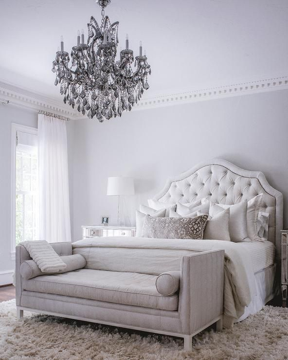 Gorgeous gray settee is placed at the foot of a white velvet tufted bed adorned with slik accent pillows and white bedding.