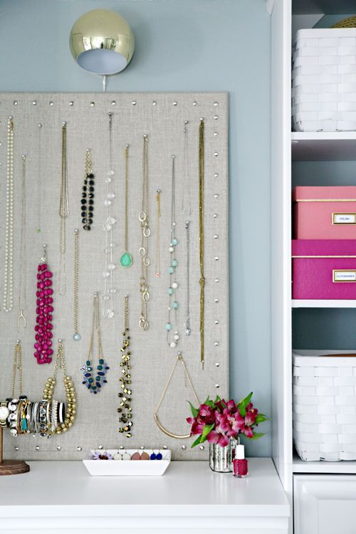 inexpensive cork board, spray adhesive, linen fabric cleanly wrapped the board and the thumb tacks added a decorative nailhead touch. Necklaces hang by basic push-pins