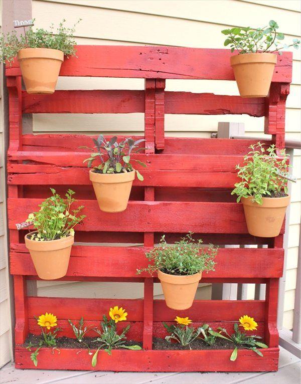 un support mural rouge avec des pots de fleurs