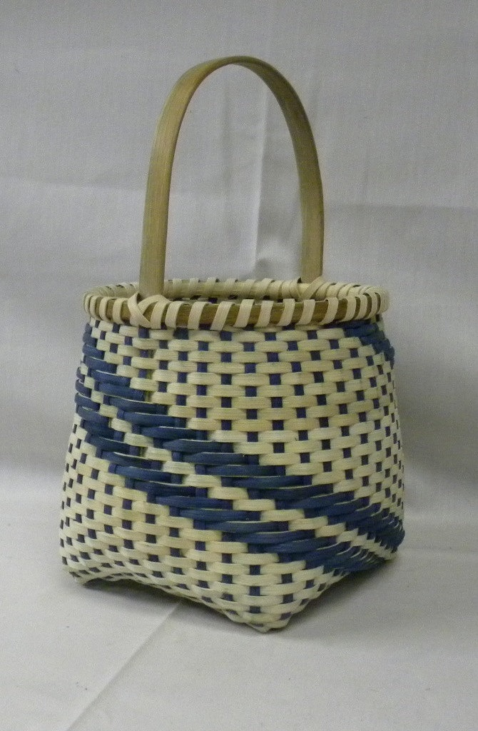 Handwoven basket with inlayed brass diamond in the handle.