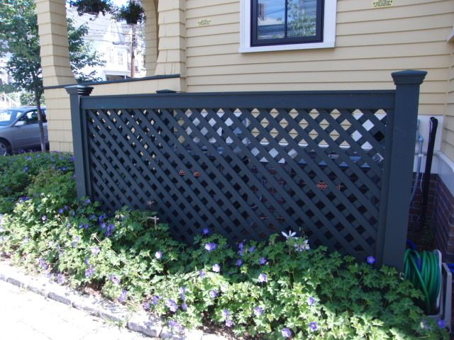 Lattice fence painted charcoal grey can hide an AC unit or trash canisters beautifully.
