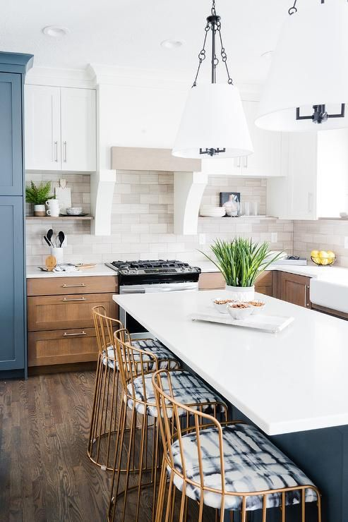 two hanging shade lights hang over a blue kitchen island seating gold metal stools at a white on kitchen island ideas white quartz id=12110