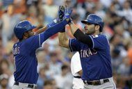 Texas Rangers' Mitch Moreland, right, high-fives teammate Elvis Andrus after they scored on Moreland's two-run home run during the fourth inning of a baseball game against the Detroit Tigers in Detroit, Saturday, July 13, 2013. (AP Photo/Carlos Osorio)