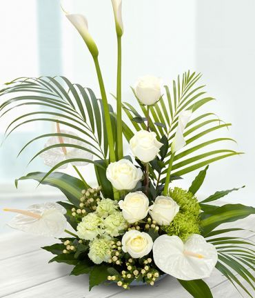 A magnificent floral centrepiece. Pure white Roses and elegant Arum and Anthurium Lilies nestled in amongst white Chrysanthemums and Carnations. Exquisitely arranged with a touch of Hypericum and a flourish of Palm.
