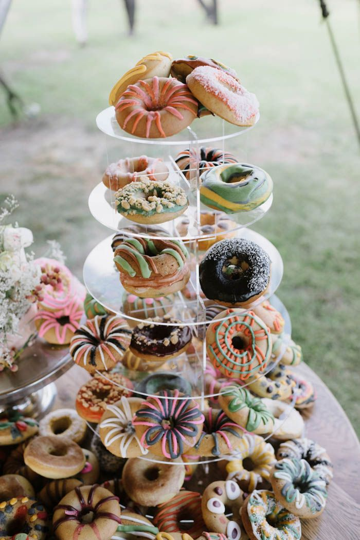 Tower of brightly colored frosted donuts in place of a traditional wedding cake | Image by Madeline Druce