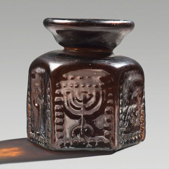 Byzantine glass flask with Jewish and Christian symbols, 6th -7th century A.D. This artifact is one of a large number of glass vessels produced in Israel and in Syria and intended for the pilgrims. Each of the six sides of the flask is decorated with a symbol,  an ornament in the form of a cross, a stylized palm tree, a shrine represented by two columns with stylized capitals supporting an arch, twice the motif of concentric lozenges and a menorah on a tripod base, 9 cm high. Private…