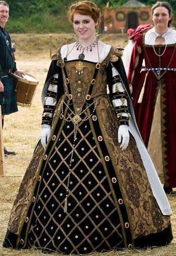 This dress was custom-made for the role of Mary Queen of Scots at a renaissance faire. The antique gold fabric is entirely beaded with freshwater pearls. There are 20 large broaches (imported from Europe) sewn into the bodice and over skirt, with over 40 smaller broaches sewn into the black velvet forepart. The velvet hanging sleeves have been pinked in a diamond pattern and are lined in silk.