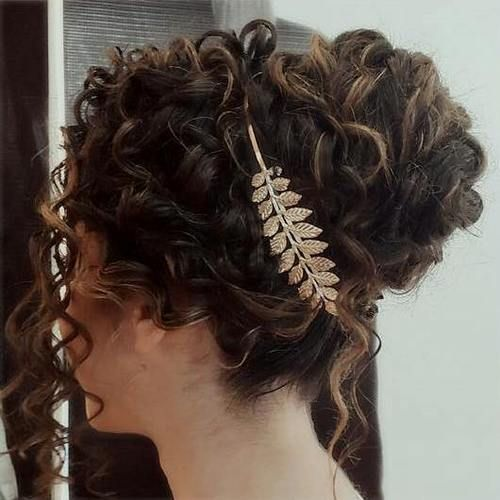 Grecian Goddess updo. Long hair is gathered into a mid-level ponytail. All of the curls are wrapped and tucked, with a few left out spirals for detail.
