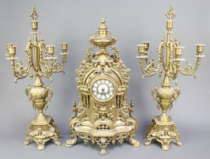 Lot 771, A reproduction 19th Century style French clock garniture comprising an 8 day striking clock contained in a gilt metal case surmounted by an urn together with a pair of 5 light candelabrum est £140-180