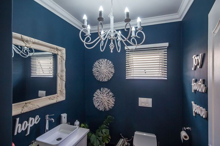 Classic white chandelier with a splash of sea blue paint on the walls.