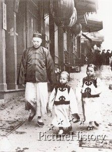Children of High Class, Chinatown, San Francisco    Lew Kan (Lee Kan) walks with his two sons Lew Bing You (center) and Lew Bing Yuen (right). Lew Kan was a labor manager for Chinese workers in the Alaskan canneries. He also operated a store called Fook On Lung at 714 Sacramento Street between Kearney and Dupont in San Francisco's Chinatown. Mr. Lew was known for his great height, being over six feet tall, and his great wealth. The boys are wearing very formal clothing made of satin with…