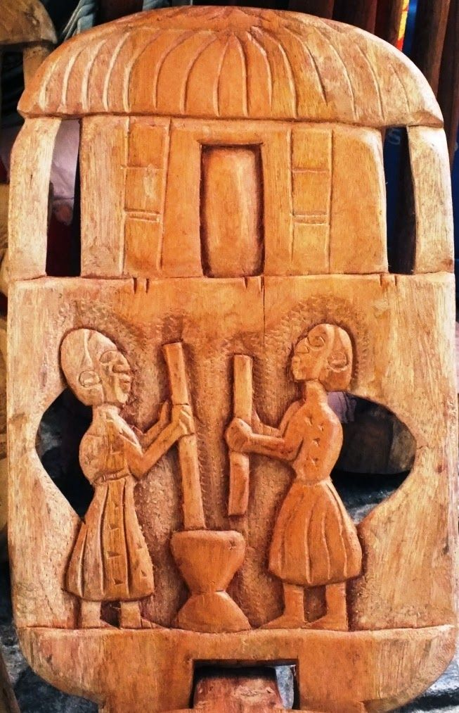African Wooden carved Chair backs showing rural family members crushing corn with the family hut at the top