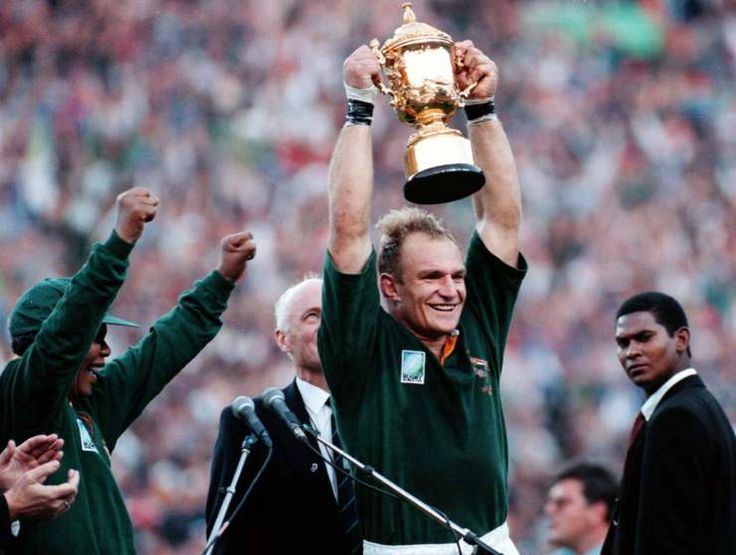 South Arican President Nelson Mandela, left, cheers as Springbok Rugby captain Francois Pienaar holds the trophy high after winning the World Cup Rugby Championship in Johannesburg on June 24 1995.
