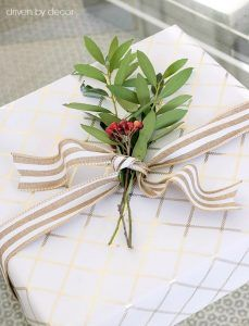 Tie a sprig of greenery and berry with ribbon when wrapping presents for Christmas