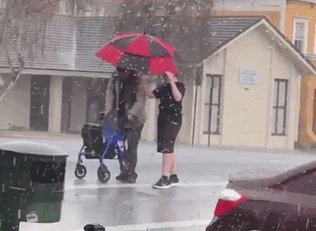 14 Year Old Boy With Umbrella Helps An Elder Cross The Street During A Hailstorm In Vallejo, California Usa