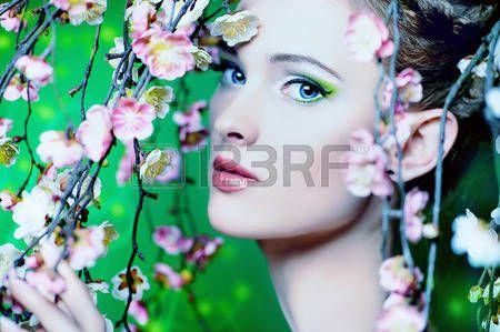 Ritratto di una bella ragazza in piedi tra i rami di fiori di ciliegio photo