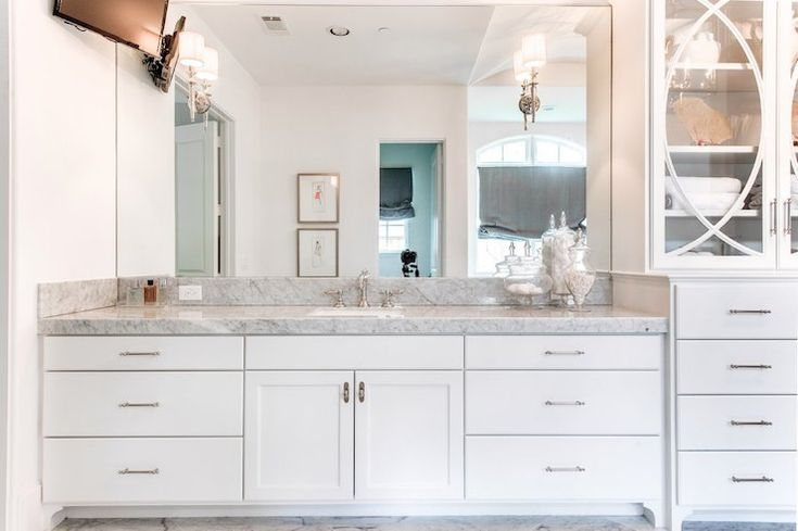 Lovely master bedroom features a glass-front center console linen cabinet next to single washstand topped with carrera marble paired with ceiling height frameless mirror lit by delicate sconces accented with TV.