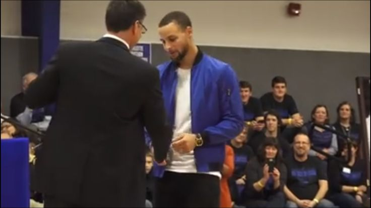 """CHARLOTTE, N.C. — Warriors star Stephen Curry looks at a jersey with his name and high school basketball number, during a halftime ceremony at his former high school in Charlotte, North Carolina. Curry's high school retired his number while Davidson College will honor him by renaming a section of its arena """"Section 30."""""""