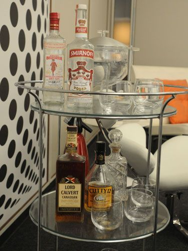rogers glass-and-steel bar features a round ice bucket, vintage seltzer bottle, and gin — the key ingredient for his go-to cocktail, the gibson.
