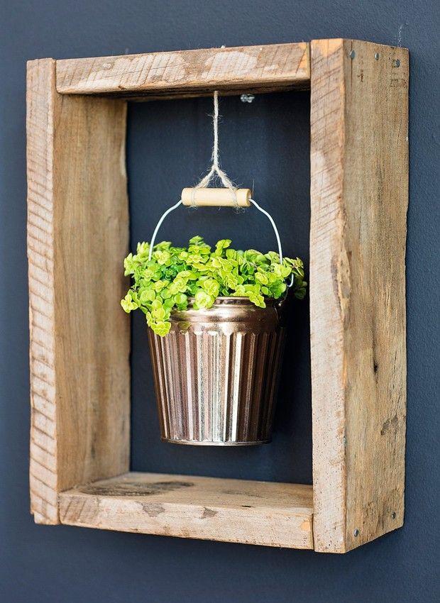 Uma caixa de madeira sem o fundo vira moldura para a folhagem no balde (Foto: Elisa Correa / Editora Globo)