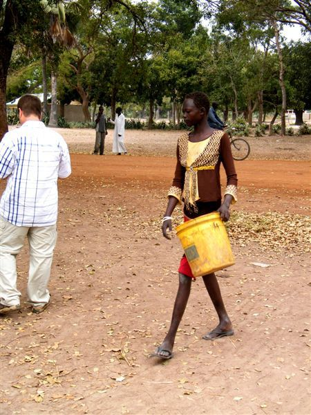 A young woman carries a water bucket.