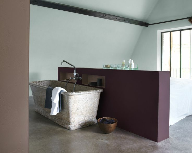 Donnez du relief au vert menthe avec un violet profond. Les murs d'un vert délicat et la baignoire en pierre donnent à cette salle de bain une ambiance onirique dont le pan de mur aubergine renforce le côté paisible.
