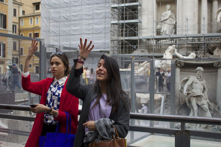 Two women, one seeming very unhappy, throwing coins in the makeshift Trevi Fountain - Rome, Italy #coins #trevifountain #italy
