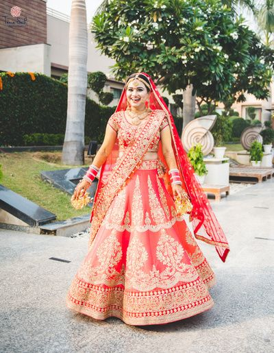 Bridal Lehengas - Coral Bridal Lehenga | WedMeGood | Happy Bride in a Monotone Coral Wedding Lehenga with Gold Embroidery  #wedmegood #indianbride #indianwedding #lehenga #coral #bridal #choli