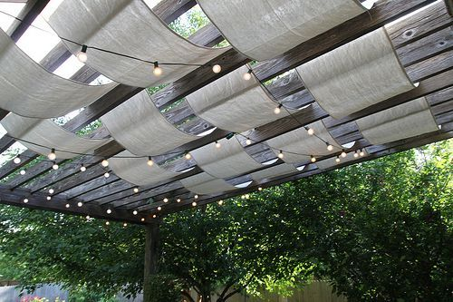 This is what we need in our backyard over the brick patio. Pergola + fabric (drop cloths) + pretty lights.