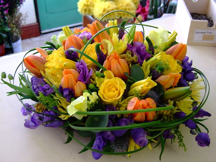 Spring posy arrangement with tulips and roses in yellow, orange and purple.