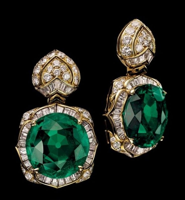 A Pair of Emerald and Diamond 'Lotus' Earrings, by Bulgari - Each pendant centering upon a circular-cut emerald, weighing approximately 11.56 and 11.37 carats, to the baguette and brilliant-cut diamond stylized lotus flower surround and top, mounted in gold, 3.2 cm, in black leather Bulgari case.  Signed and with maker's mark for Bulgari - Estimate:  $396,662 - $594,993 - Christie's Magnificent Jewels Sale, Geneva 2014. (=)