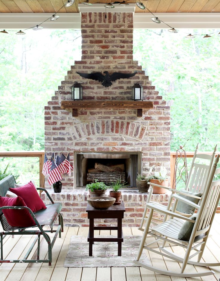 On the back deck, which overlooks a wooded area and stream, salvaged brick features prominently around the wood burning, gas starter fireplace by Lennox. Rocking chairs are from Unpainted Furniture Center, the table was built by Bret's grandparents and the glider is vintage.
