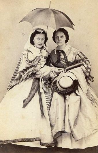 Two fashionable young ladies & only one parasol. Quite an array of accessories! Shawls, hat, silk mantle/paletot over the arm...