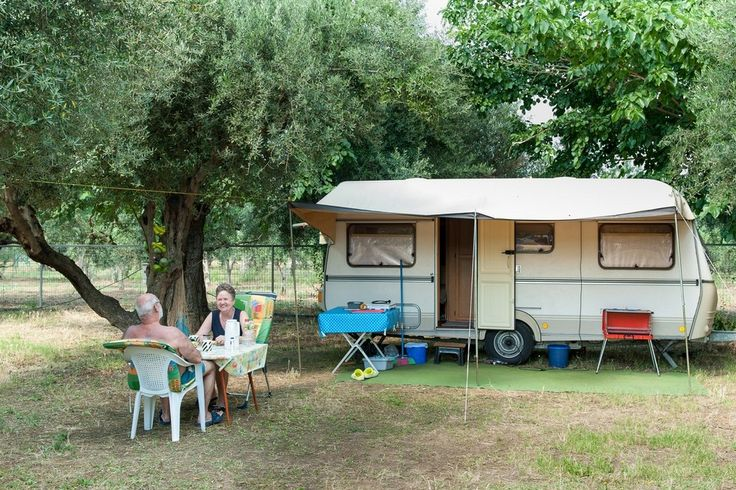 People relaxing with their caravan on the campsite