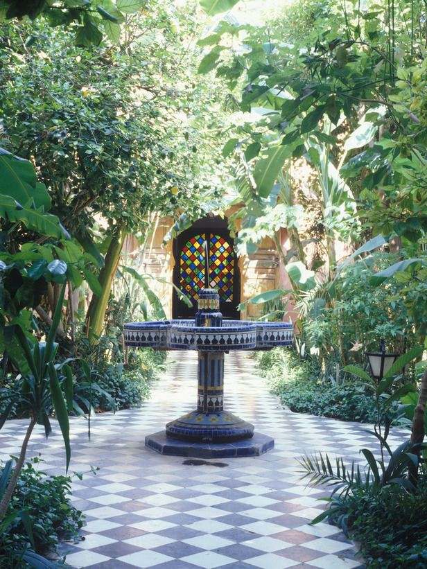 Moroccan Charm-  In this courtyard inspired by North African style, lush planting forms a backdrop to the elegant tiles and raised water bowl.