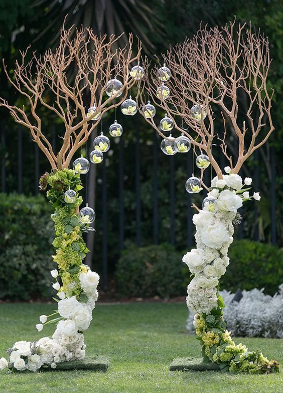 Branches create an archway with lovely white & green flower arrangements and hanging glass bubbles / http://www.himisspuff.com/wedding-arches-wedding-canopies/4/