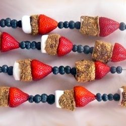 S'mores skewers - chocolate dipped marshmallows covered in graham crackers with strawberries and blueberries.