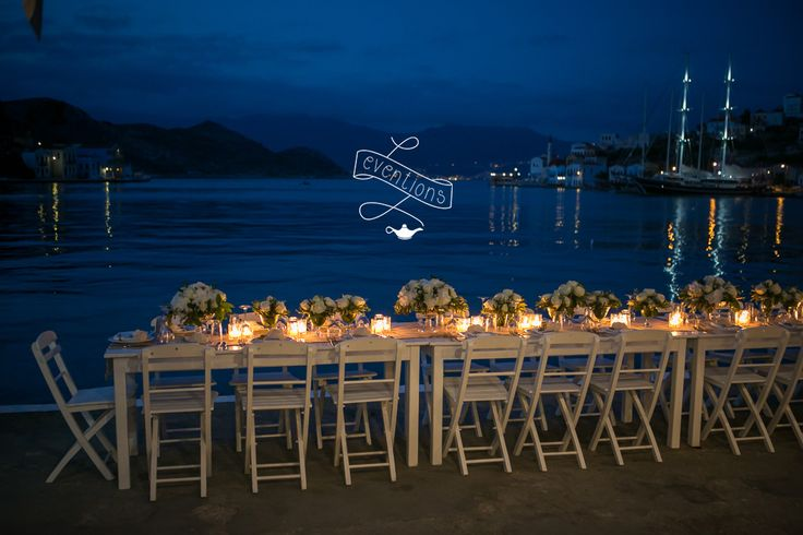 Dinner table full of white flowers and candles, for a wedding in Kastellorizo island. Collaboration with the12events.