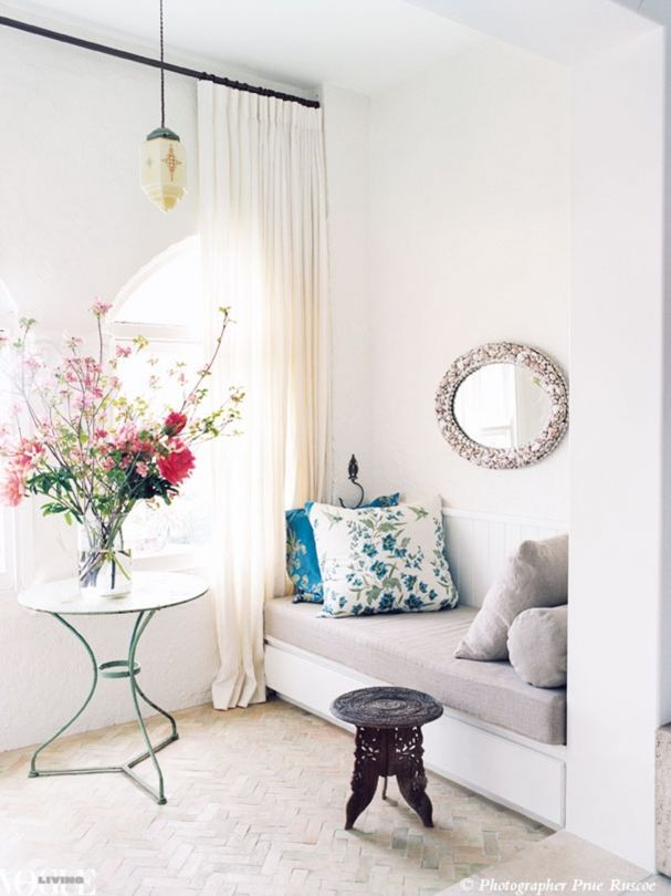 Entries, hallways and stairwells: how to make the most of every corner: A custom bench seat with patterned cushions side table makes the most of this sunny window sill.