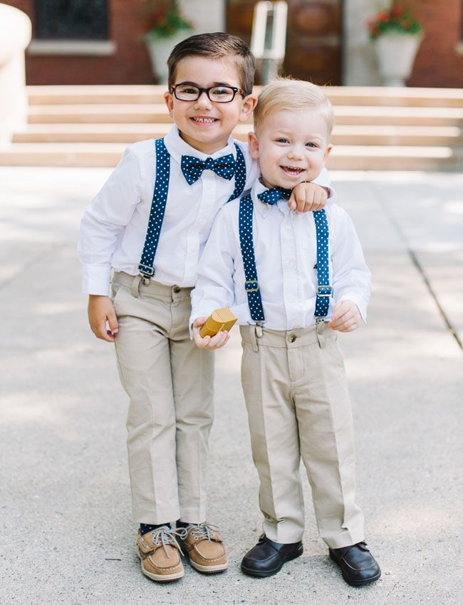 Dapper little page boys in navy blue polka dotted suspenders and bow ties.