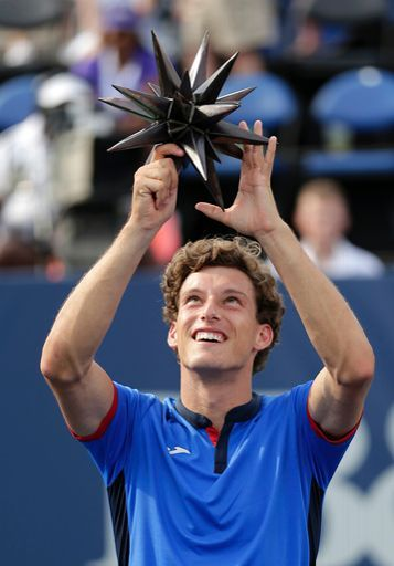 Pablo Carreno Busta, of Spain, holds up the trophy after winning the Winston-Salem Open tennis tournament over Roberto Bautista Agut, also of Spain, in Winston-Salem, N.C., Saturday, Aug. 27, 2016. (AP Photo/Chuck Burton)