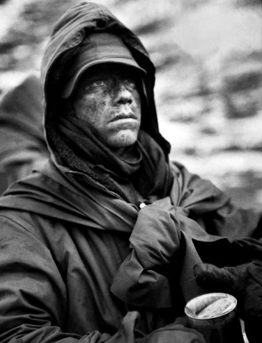 A dazed, hooded Marine clutches a can of food during his outfit's retreat from the Chosin Reservoir during the Korean War, December 1950.