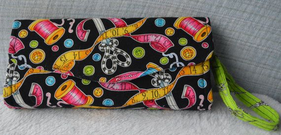 A Fabric clutch wallet that fits everything! Perfect as an everyday, on the go wallet!  12 card slots (two 6 slot sections, ample enough for multiple cards in the same slot but still tight enough for just a single card!) 2 cash/cheque pockets (behind the card slots), a zippered coin pouch (sized to be able to hold onto your lip gloss on top of a huge handful of coins) and extra divider for everything you need to hold onto. This space is large enough for even a large sized smart phone AND...