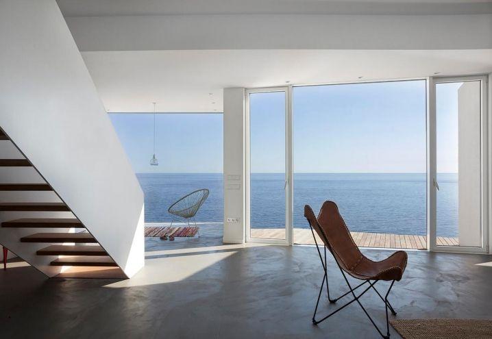 Dal living si accede a un deck panoramico rivestito da listelli in legno: la vista si apre sul mare. Il pavimento in microcemento grigio ospita la tripolina Butterfly Chair (a sinistra), la poltroncina Acapulco e il tappeto realizzato a mano